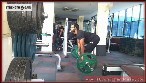 Man looking up while doing a barbell exercise